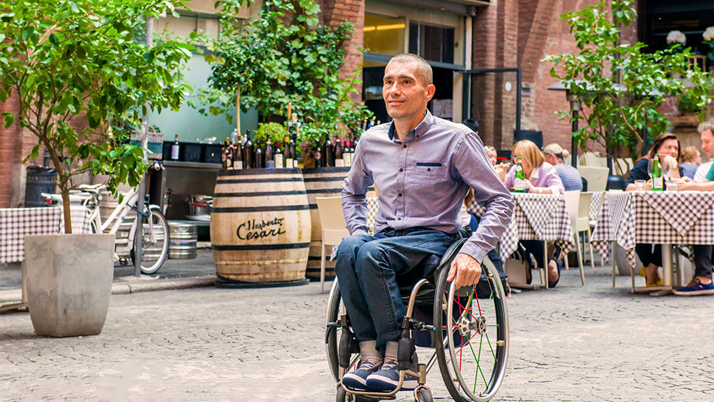 Wellspect Lofric Man in wheelchair outdoors in Italian city location